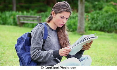 Smiling young woman studying in a park