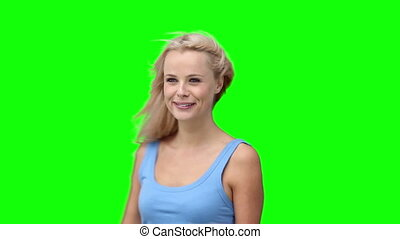 Blonde woman dancing with her arms raised against a green...