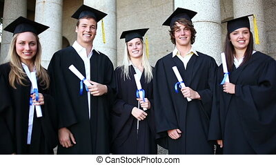 Students laughing while holding their diplomas in front of...