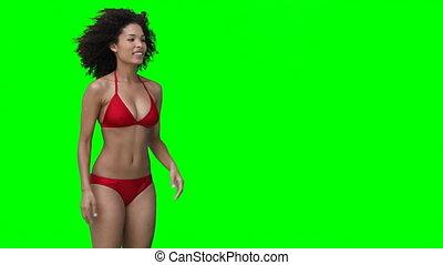 A smiling woman throws a beachball off screen against a...