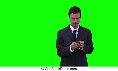 Businessman typing on his phone while looking around him...
