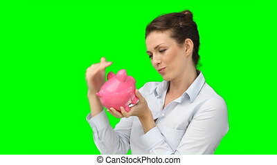 A smiling woman kissing her piggy-bank while against a green...