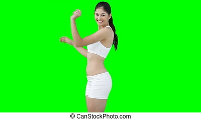 A woman dancing as she shows off her figure against a green...