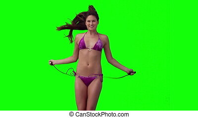 Woman using a skipping rope against a green background
