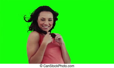 A smiling woman is playing with her hair against a green...