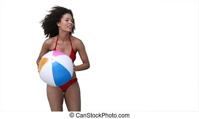 Woman playing beachball in her bikini against a white...