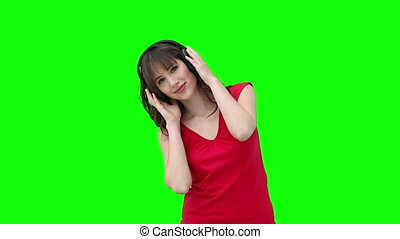Woman holding headphones while listening to music