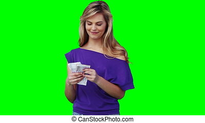 A woman holding a lot of cash in her hand and smiling