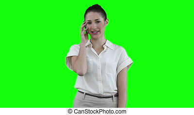 Woman making a call against a green background