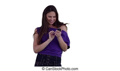 Woman smiling while typing a text message against a white...