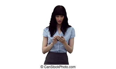 Businesswoman typing a text message before looking around her