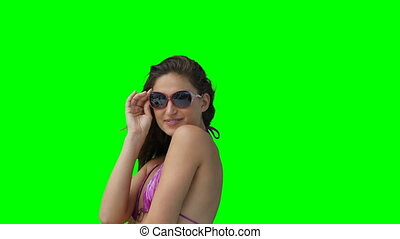 A woman posing with her sunglasses against the green...
