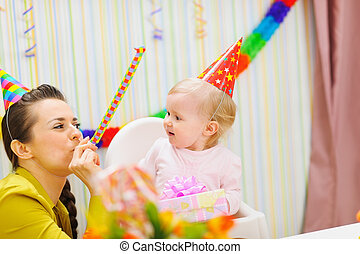 Mother and baby having fun at birthday party