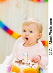 Surprised baby eating first birthday cake