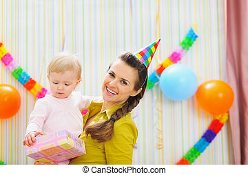 Portrait of happy mom and baby with birthday gift