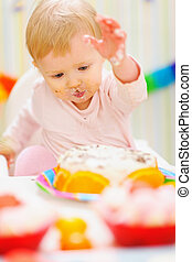 Eat smeared baby having fun with birthday cake