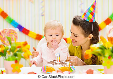 Portrait of happy mom and baby eating birthday cake