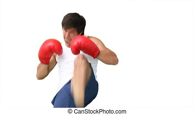 A man practising his kick-boxing against a white background