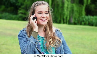 Cheerful woman using her mobile phone in a park