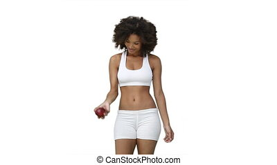 Woman in training clothes throws an apple upwards against a...