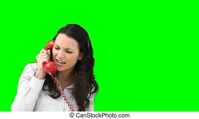 A woman arguing on the telephone against a green background