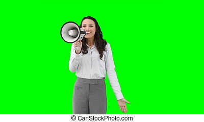 A woman using a megaphone to talk against a green background