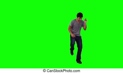 A man is dancing on his own against a green background