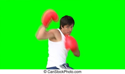 A man practises kickboxing against a green background