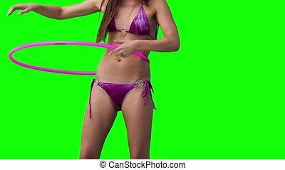 Woman spinning a hula hoop against a green background