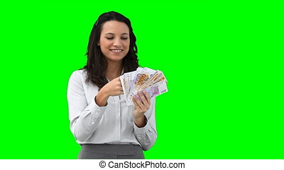 A business woman uses money as a fan in front of a green...