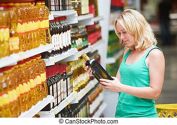 woman making grocery shopping - woman choosing bio food...