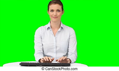 A woman typing on her keyboard against a green background