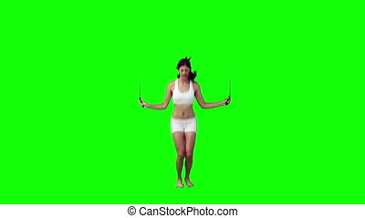 A woman is jumping with a skipping rope against a green...