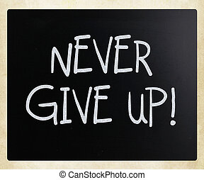 """Never give up"" handwritten with white chalk on a blackboard"