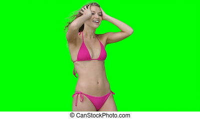 A woman in a bikini posing against a green background