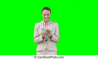 A smiling woman counts and shakes all of her money against a...