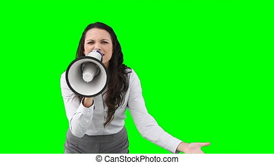 A business woman roaring through a megaphone in front of a...