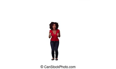 An excited woman is energetically jumping against a white...