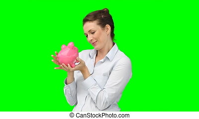 A woman kissing and cherishing her piggy-bank against a...