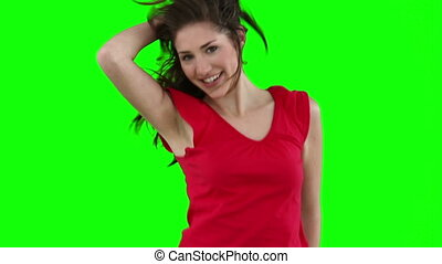 Woman jumping while stroking her hair against a green...