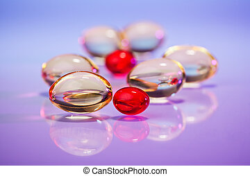 Pills (capsules) of cod-liver oil on violet, macro view with...
