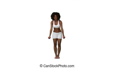 A woman is standing lifting hand weights against a white...