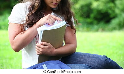Smiling woman holding notebooks in a park