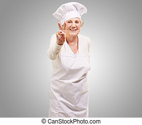 portrait of cook senior woman doing approval gesture over grey background