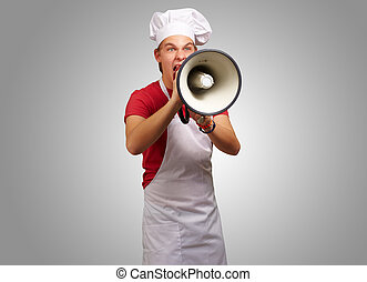 portrait of young cook man screaming with megaphone over grey background
