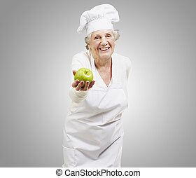senior woman cook offering a green apple against a grey...