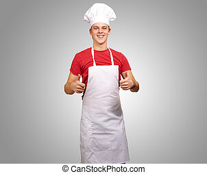 portrait of young cook man doing success symbol over grey background