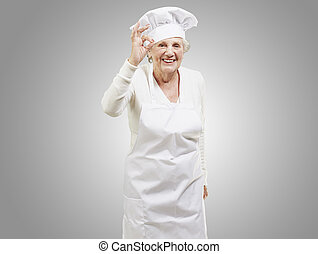 senior woman cook doing an excellent symbol against a grey...
