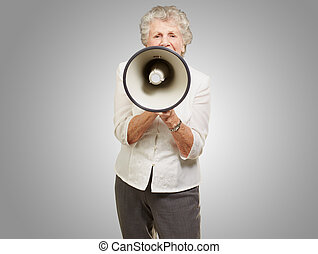 portrait of senior woman screaming with megaphone over grey...