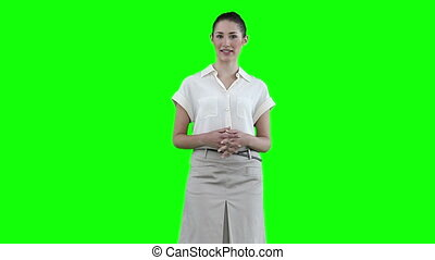 Businesswoman making an announcement against a green...